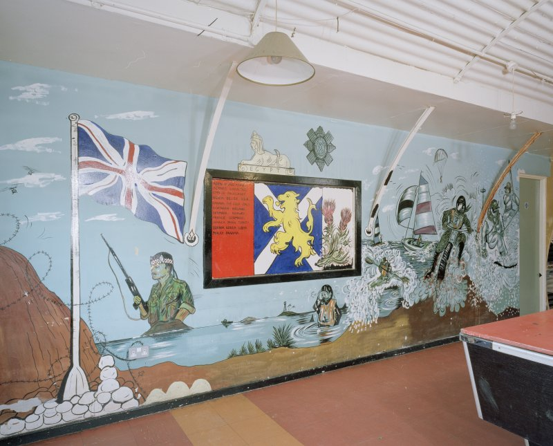 Interior view of NAAFI (hut 65), view of wall painting (cartoon) on wall showing regimental badge, colours and list of bases round the world