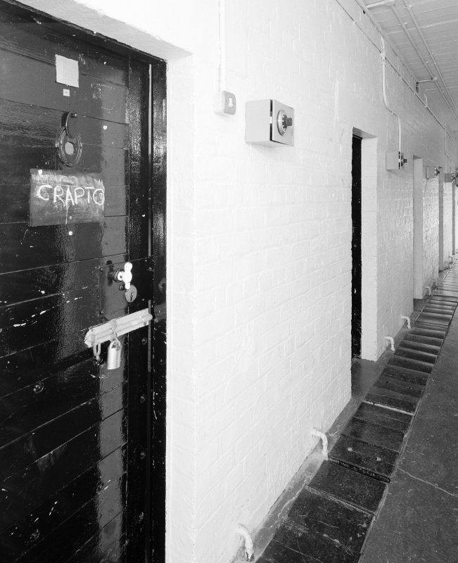 Interior view of armoury/main camp store showing corridor and former cell doors
