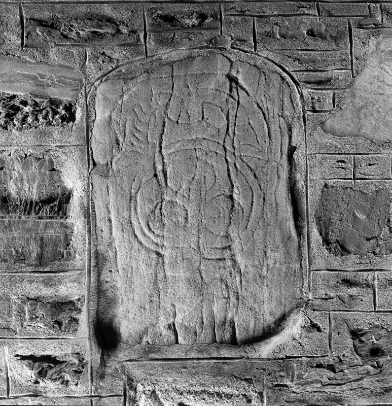 General view of Tocherford Pictish stone bearing an unusually curved variant of the horse-shoe symbol above a disc enclosing three smaller circles.