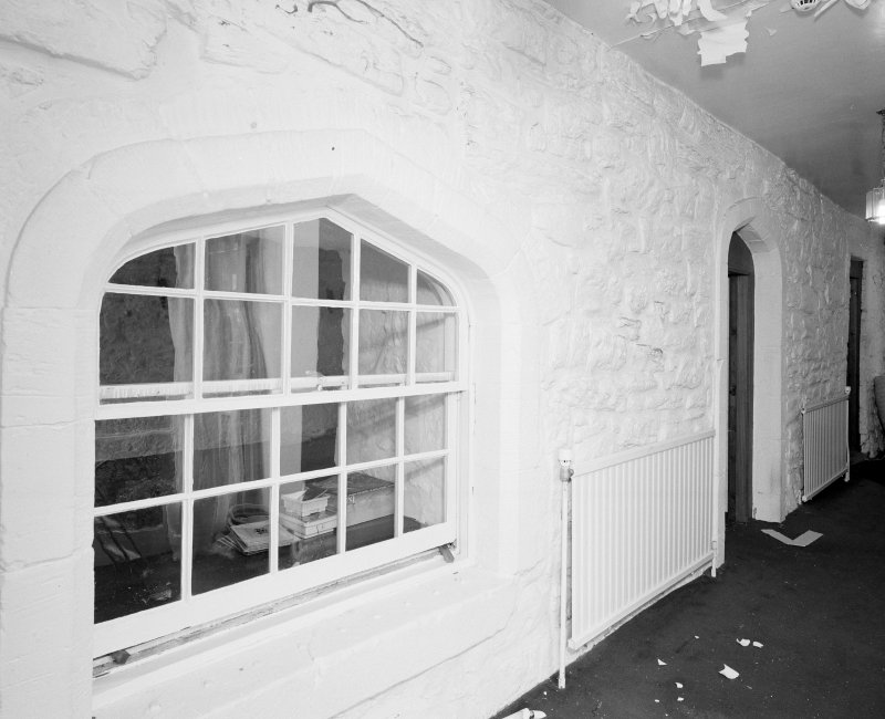 Interior. Ground floor entrance hall showing S wall of tower with arched openings