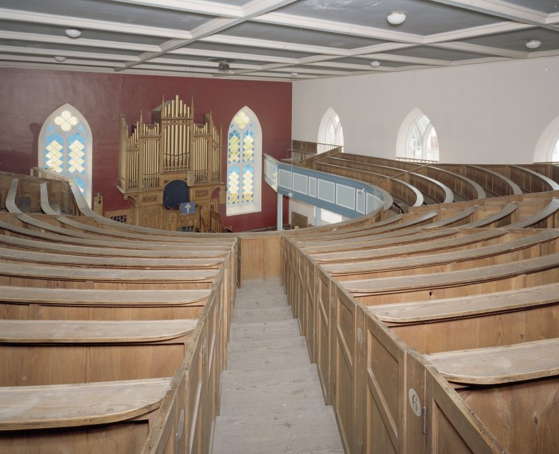Interior. Gallery  view from S showing curved raked pews
