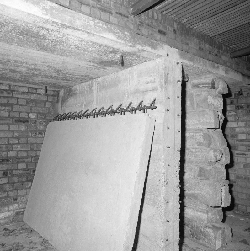 E/W Track. Hut interior with large hinged concrete door and brick partitions