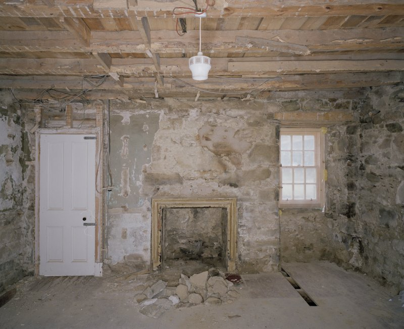 Interior. N range, ground floor, W room W wall with fireplace