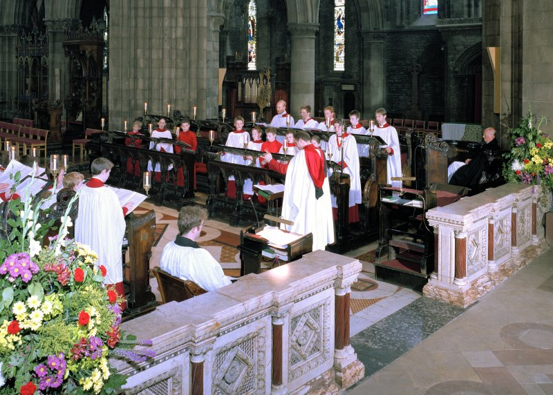 Interior. View showing entrance to choir with director of music conducting choristers.