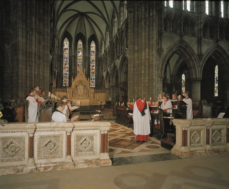 Interior. View of choir and apse ended chancel with director of music conducting choristers.