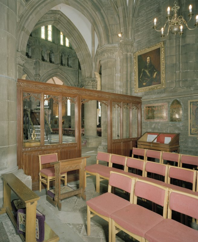 Interior. View of carved timber screen separating NW transept from aisle of nave.