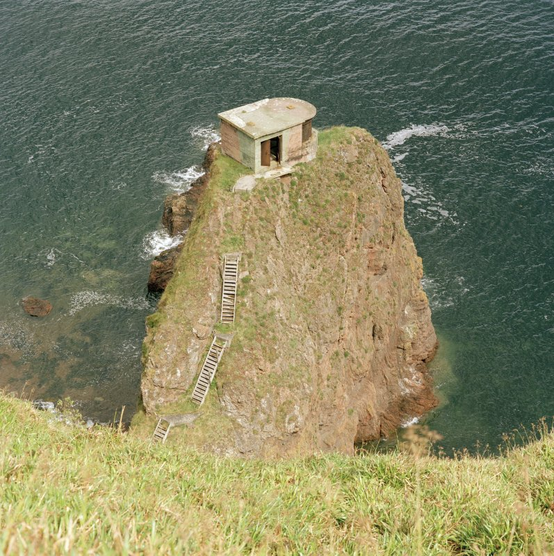View from SW over cliffs to searchlight emplacement on rock stack.  Also visible are sections of timber access steps.