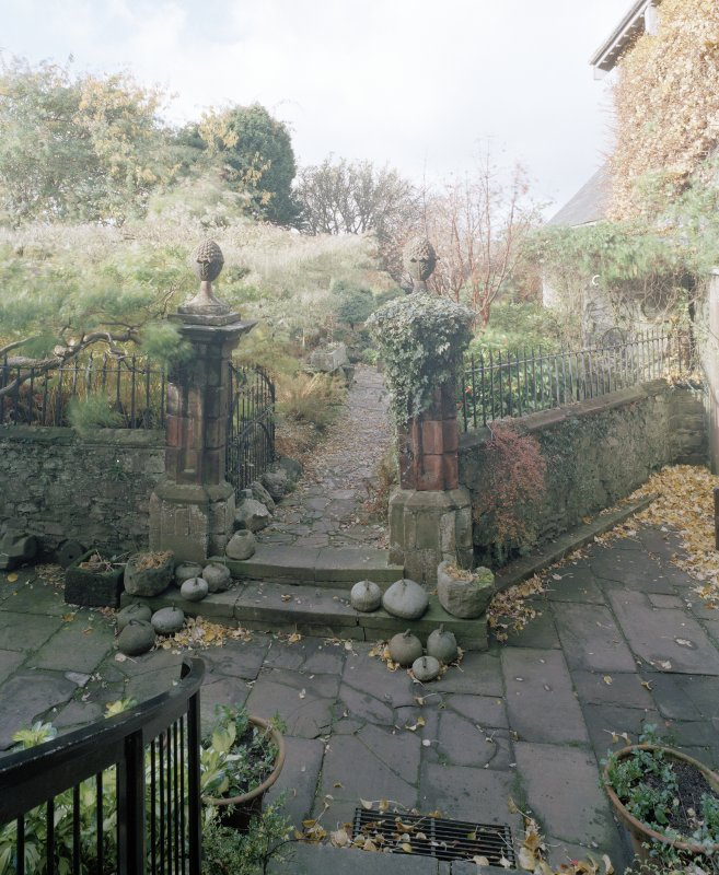 View of entrance to garden showing coutyard and 18th century pineapple finialed gatepiers