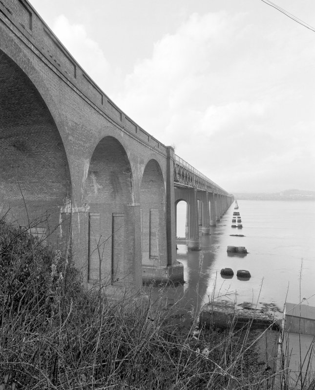 Oblique view from SSE of E side of bridge, with brick viaduct arches in foreground, and main part of bridge in the background.  The foundations of the piers of the earlier bridge are also visible (right)