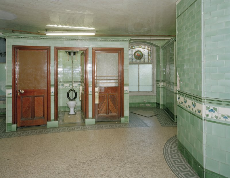 Interior. View one of two blocks of three cubicles.  All the original water closets and cisterns appear to have been removed, but most cubicles retain the green tilework.  Also visible (right) is a surviving stained-glass window.