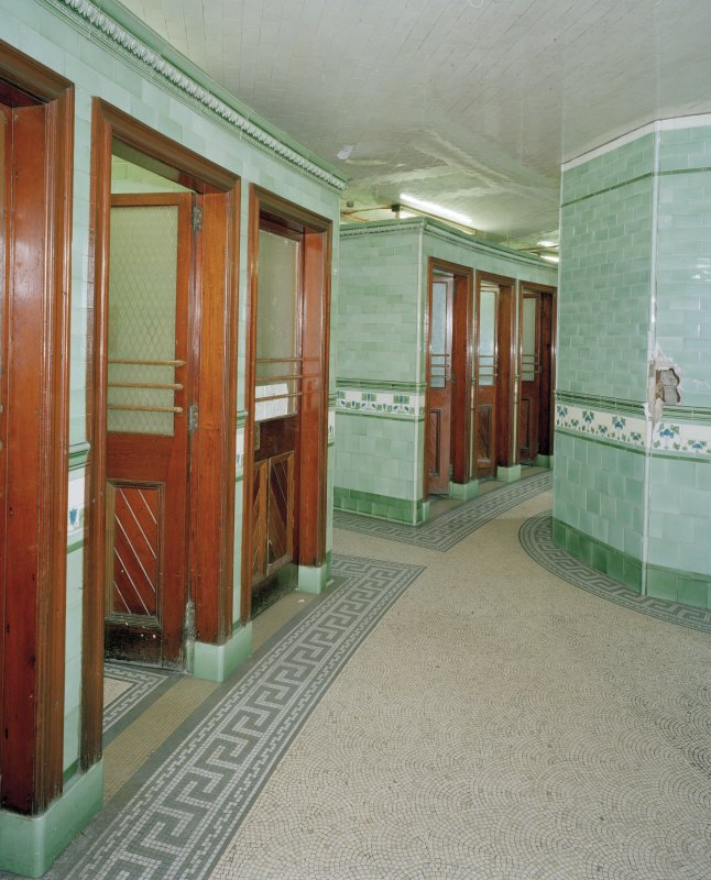 Interior. View of the two blocks of three cubicles, a further pair of cubicles being located beyond (out of picture).  All the original water closets and cisterns appear to have been removed, but most cubicles retain the green tilework.