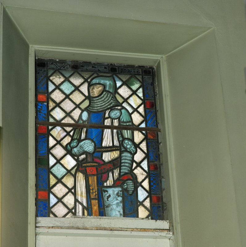 View of reused stained glass window depicting a knight to West of the organ.