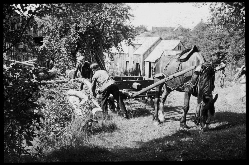 Unidentified location showing men working with horse-drawn cart/machinery.
