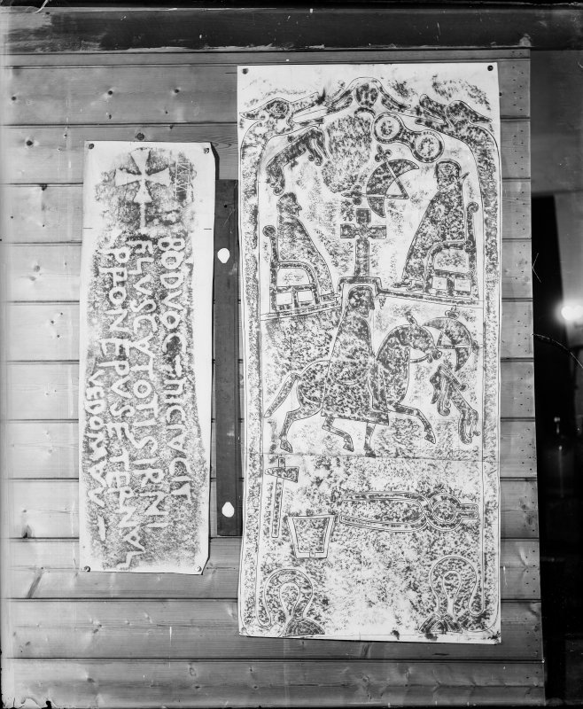 Photographic copy of two rubbings. The left rubbing is the inscribed carved stone, known as the 'Badvoc Stone', originally from Margam Mountain, now re-housed at Old School House Margam, Glamorgan, Wales. The right rubbing is the reverse of Dunfallandy Pictish cross slab.