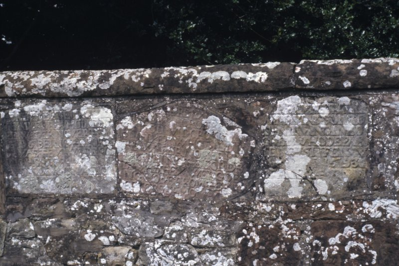 Detail of engraved stones in churchyard wall, one is dated 1593, Canonbie Parish Church.