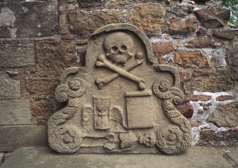 View of tomb fragment with winged hourglass, scroll, skull and skeleton, Elgin Cathedral.