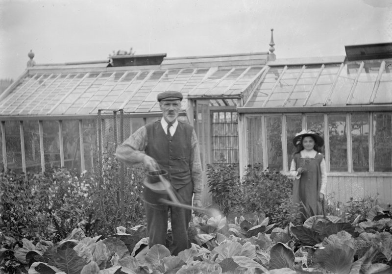 View of a man and a girl in a vegetable garden, possibly at East Silvermills Lane Ironworks, Edinburgh.