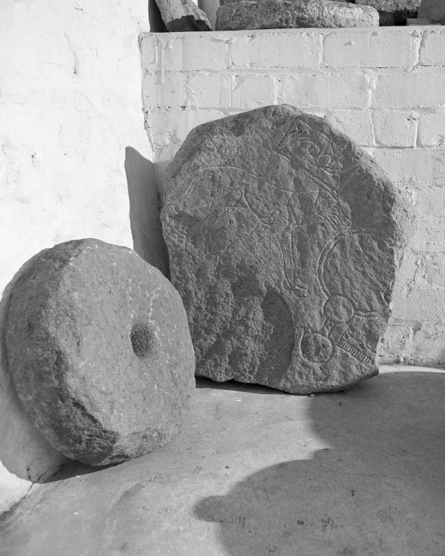 View of the Wolf Stone and a quern stone in the garden of Leith Hall. The Pictish symbol previously stood at Newbigging Farm, Leslie.