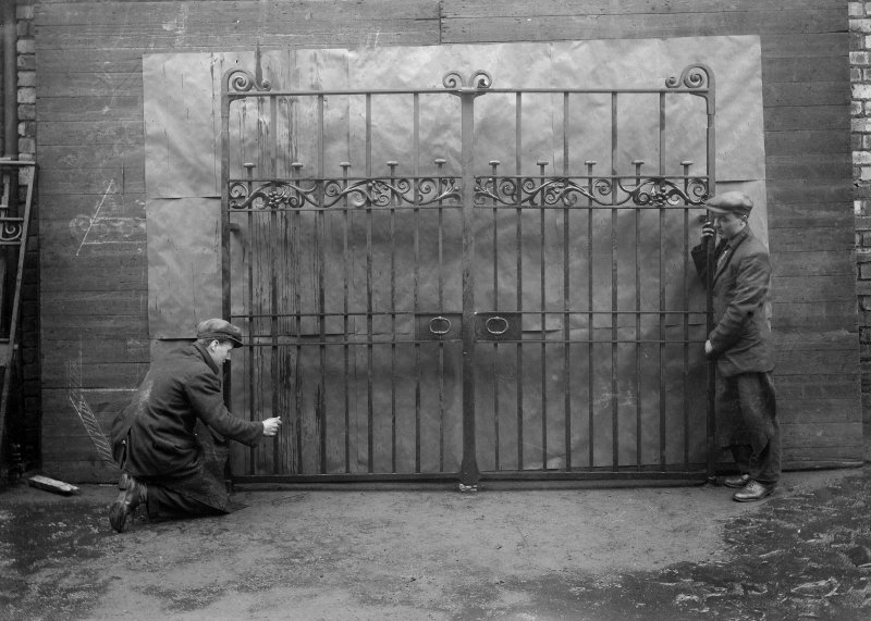 View of wrought iron gates and two workmen.