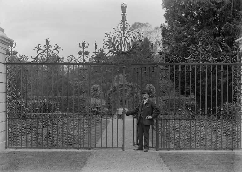 View of man by unidentified wrought iron gates.