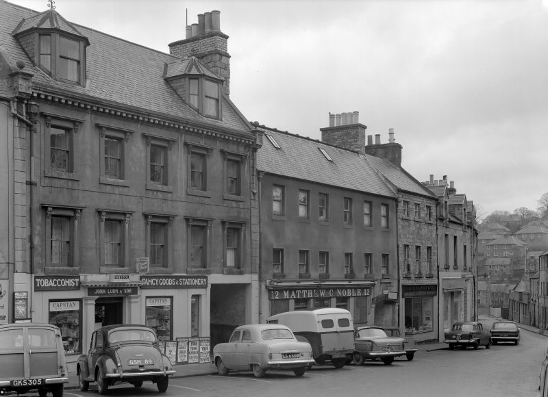 View of south elevations of 10 -16 Canongate, Jedburgh from west, showing the premises of John Luhn & Son, Matthew C Noble and J C Clark & Co