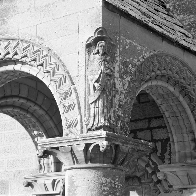 Detail of carved figure on entrance porch on S facade.