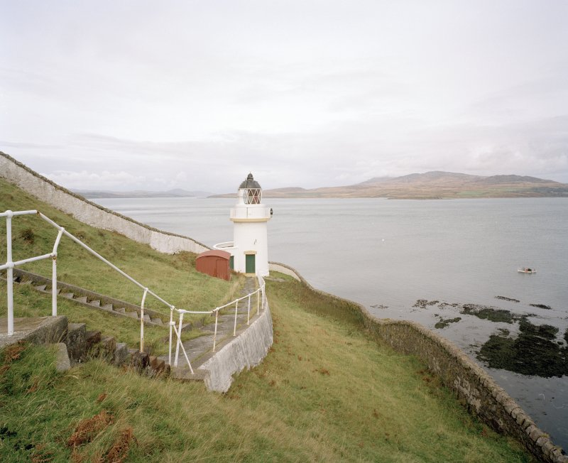 Islay, McArthur's Head Lighthouse View from S within compound, showing steps down to lighthouse, the compound wall, and the Sound of Islay in the background, with Jura also visible across the water