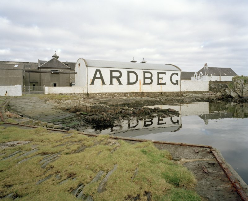 Ardbeg Distillery View from S of S (seaward) side of distillery, showing bonded warehouse bearing the name 'ARDBEG' in large letters, designed to catch the eye of passing ferry passengers