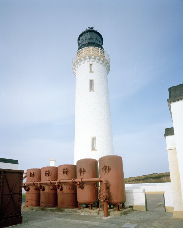 Detailed view from SE of lighthouse tower, with battery of five dome-ended air receivers (in the foreground) which stored compressed air (generated in the fog-horn engine house to left) to power the fog horn.  Note the two receivers to the right are welded, and the three to the left are riveted.