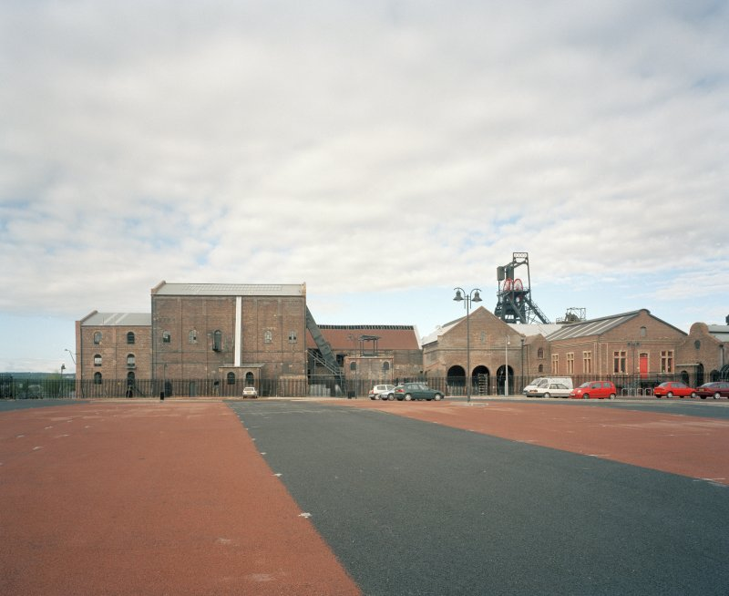 General view of S portion of colliery surface buildings from E following the demolition of the north end of the neighbouring workshops and the construction of a carpark for the museum.