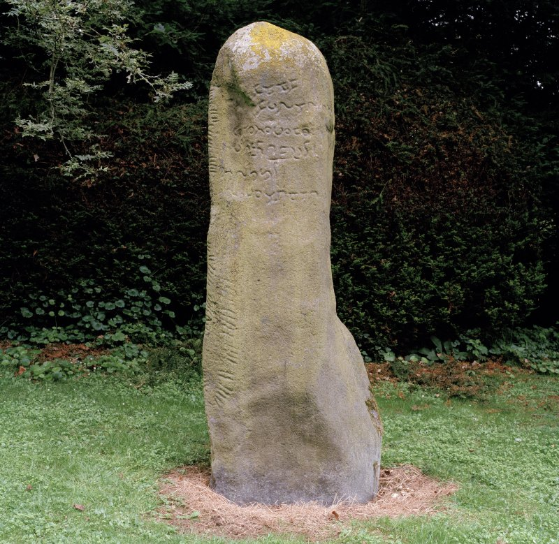 View of inscribed stone, showing inscription on face and ogham inscription along edge (flash-lighting).