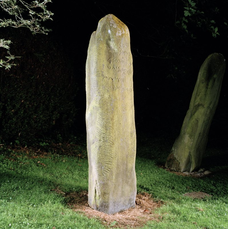 View of inscribed stone, from side, showing inscription on face and ogham inscription along edge (flash-lighting).