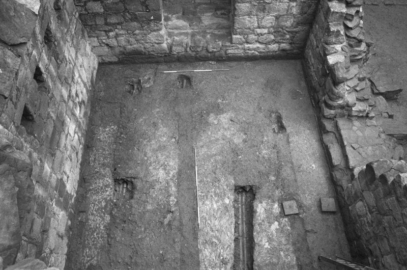 Excavation photograph : floor of tower house basement viewed from above, from N.