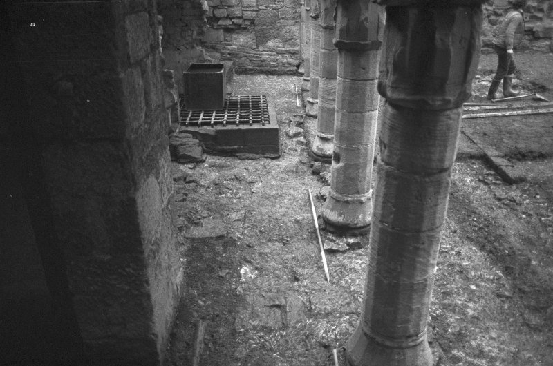 Excavation photograph : W end of trench on N side of courtyard showing remnants of demolished wall F36 below row of columns, from W.