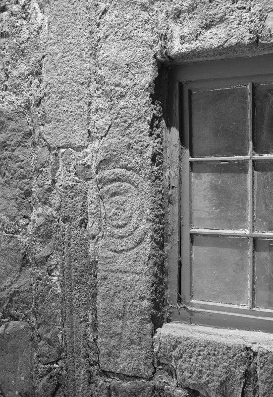 View of face of fragmented Pictish symbol stone, used as lintel above a window at East Balhalgardy Farm.