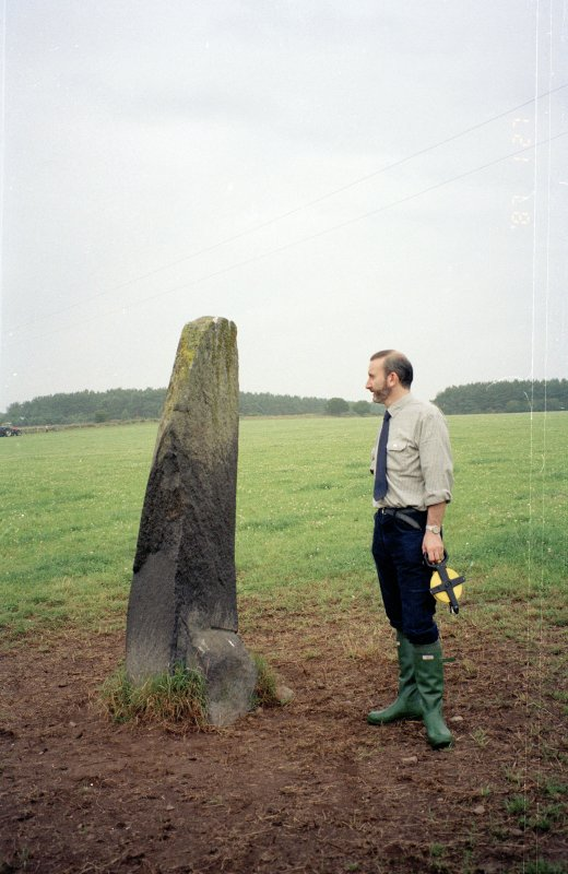 View of rubbing stone from E, with Dr Iain Fraser (RCAHMS) in picture