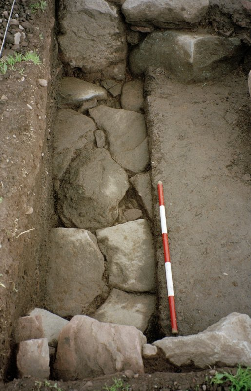 View from W of paving at N end of the excavation trench. Scale in 200mm divisions