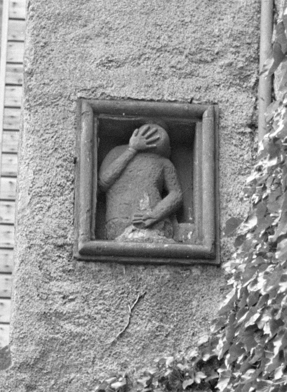 Fyvie Castle. Detail of panel showing upper body with hand covering face on 18th century buttress.