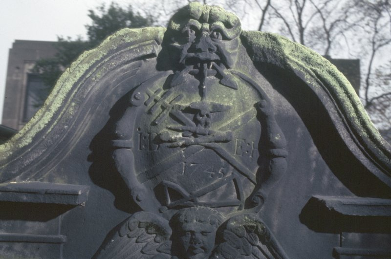 Detail of headstone showing Green Man with anchor in mouth and tools below, North Leith  Parish Churchyard, Edinburgh.