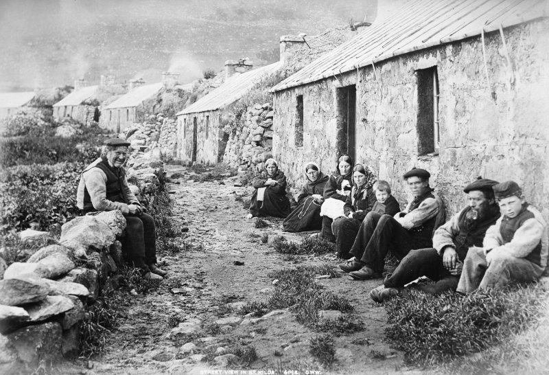 St Kilda Village. View of group of villagers sitting  in street.