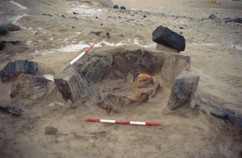 Excavation photographs: Bronze Age cist burial under excavation. Includes detailed views of skeleton and pottery vessel.