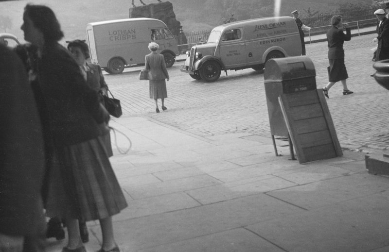 View of Princes Street, Edinburgh at time of the Coronation of Queen Elizabeth II showing pedestrians, a Lothian Crisps van and a van for Alexander Orman, joiner and builder.