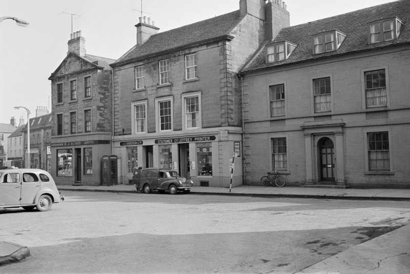 View of 47-50 Market Square, Duns, from north showing the premises of R J Glover Ladies and childrens outfitter, A & G Anderson Ltd and Geo Jeffrey Stationer and Printer