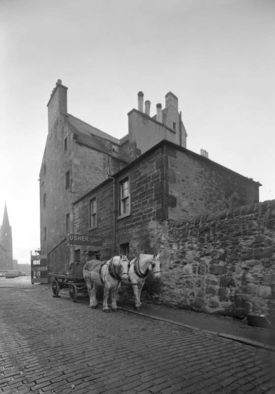 View of the side of 104 St Leonard's Street, Edinburgh including Castle o' Clouts seen from the entrance lane to Usher Brewery from NE, showing horse-drawn cart.