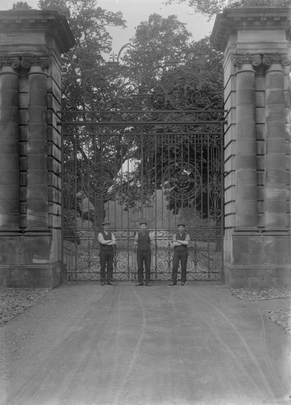 View of three men in front of unidentified entrance gates with heraldic design and the date 1893