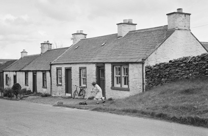 View of south side of Victoria Street, Kirkpatrick Durham, from north west, showing a woman cutting grass outside no.53