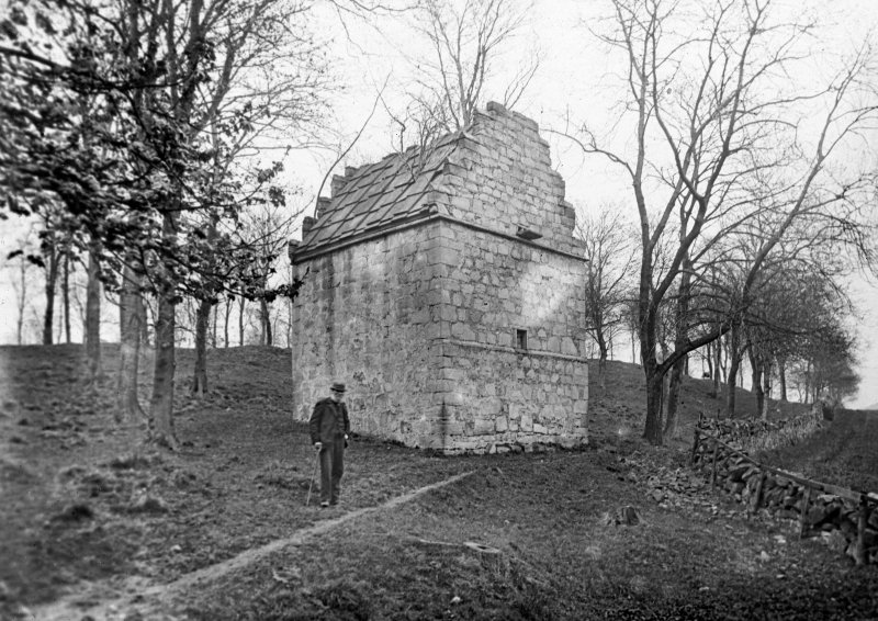 View of dovecot at Rosyth Castle from WSW with an elderly man standing beside it.