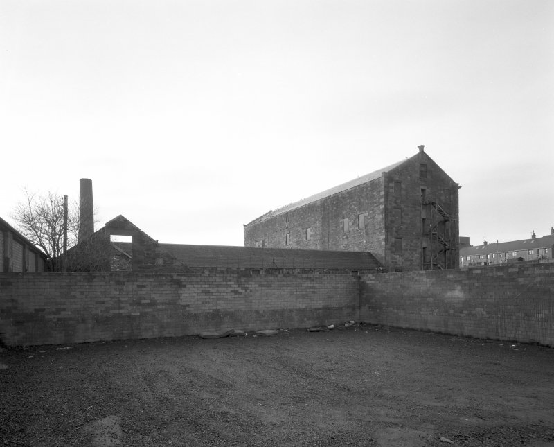 General view of works from NE, showing boiler-house chimney and E side of high mill, with N side of single-storyed shed.