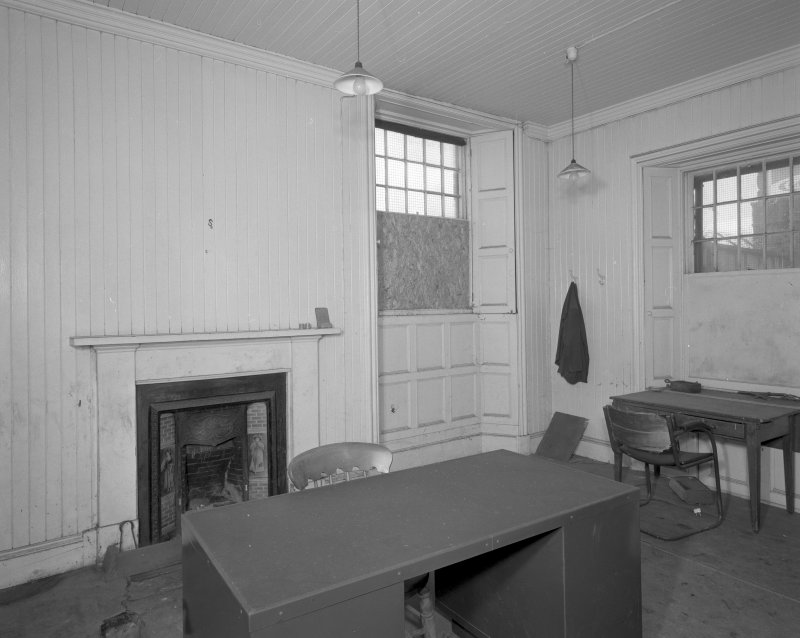 Interior. View of office, showing fireplace and tongued and grooved wood panels and shutters.