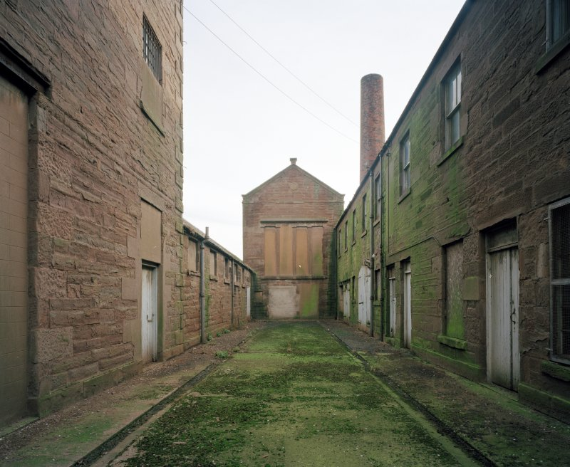 View from W showing west elevation of former engine house, offices and cooperage, and high mill.